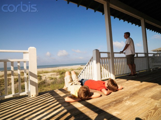 Father and Two Sons Relaxing on Porch of Beach House
