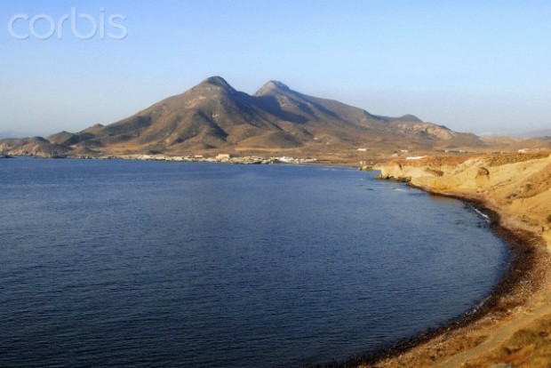 Spain, Andalusia, province of Almeria, Cabo de Gata-Níjar Natural Park, the coast seen from the village la Isleta, with the silhouette of Cerro del Fraile, volcanic mountain, in the background