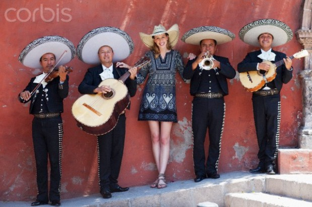 Smiling female tourist wearing sombrero standing together with Mariachi Band